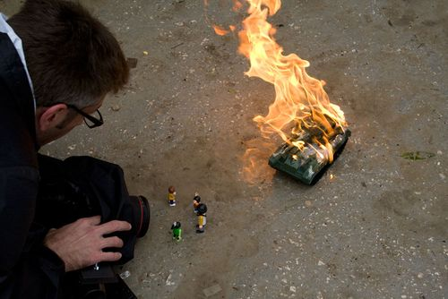 child playing with a toy tank and burning toy soldiers